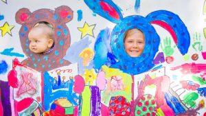 lapset kurkistavat maalauksen aukoista