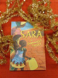 Sara ja kadonneet sateet -kirja punaisella pohjalla.