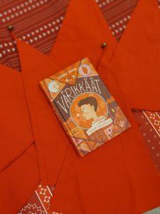 Värikkäät-kirja punaisten tonttulakkien päällä.