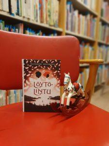 Löytölintu-kirja punaisella tuolilla vieressään pieni keinuhevonen.