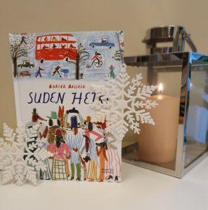 Suden hetki -kirja vieressään kynttilälyhty ja lumihiutaleen muotoisia joulukoristeita.