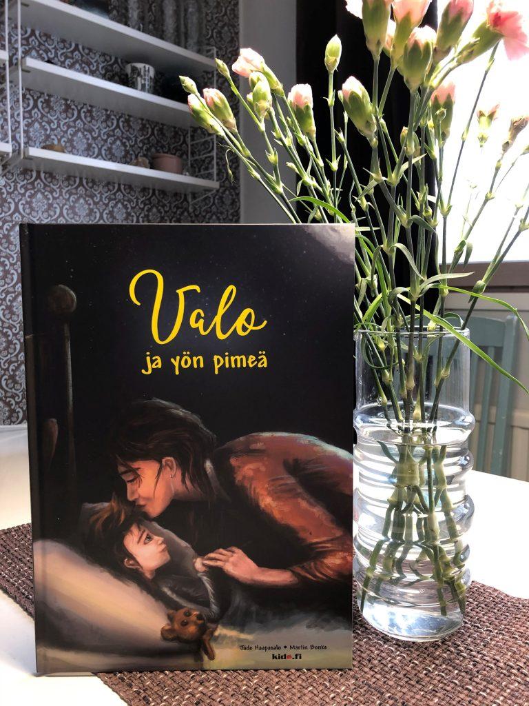Valo ja yön pimeä -kirja, jonka vieressä kukkamaljakko.